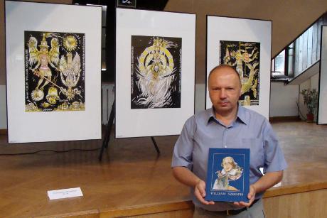 Zbigniew Kołaczek z  katalogiem wystawy na tle swoich prac